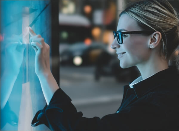 A woman stands at a digital screen